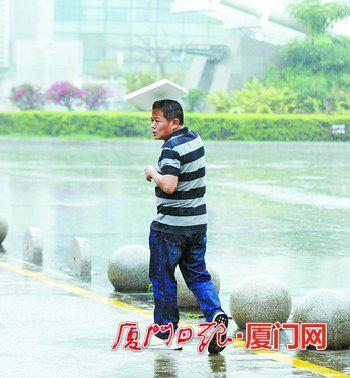 昨日,一名没带伞的行人用塑料板遮雨。