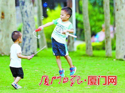 天气闷热,孩子们来到公园玩乐。(本报记者 张奇辉 摄)