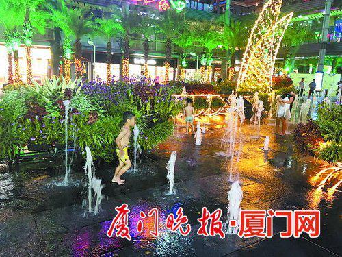 ■小朋友在喷泉区玩耍,家长在外围看手机或闲聊。