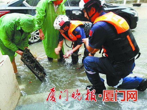 市政人员和蓝天救援队队员打开箅子,加速路面排水。