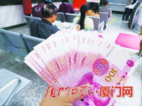 ▲前日,一位市民从银行取出崭新的钞票。