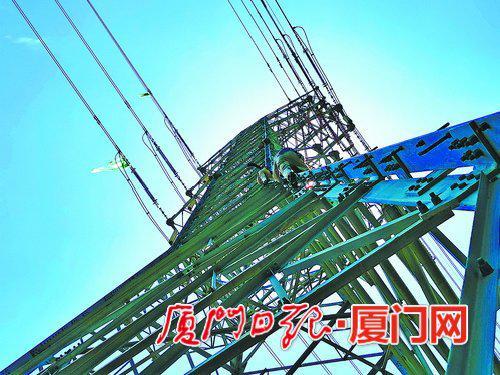 供电公司带电作业班电力人员在同安区滨海西大道的220千伏铁塔上进行高空作业。 (陈国信摄)