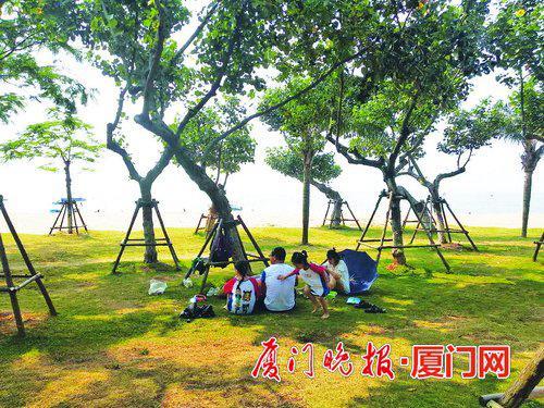 ■草地上,不少人席地而坐。