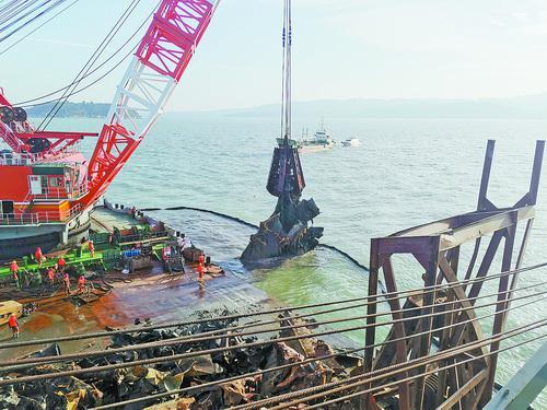 抓住船体残骸后,起重船慢慢起吊出水。