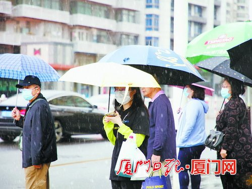 昨日降雨气温下降,出行市民穿起了外套。(蔡茂祥摄)