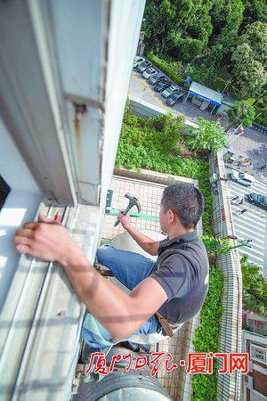 空调师傅悬空在外,腰上系着一条安全绳,泰然自若地安装外机。