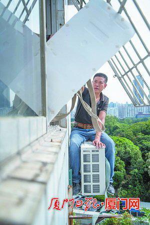 空调师傅用空调箱中的泡沫板临时顶开防盗网,坐到户外安装外机。