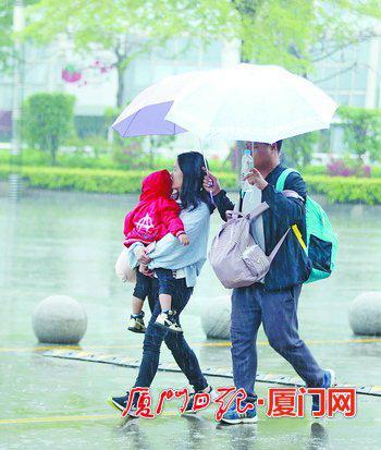 昨日,一名行人在雨中撑起两把伞,一?#36805;?#25265;孩子的家人,一?#36805;?#33258;己。