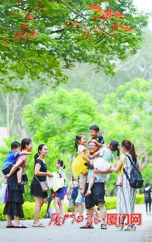 昨日天气闷热依旧,时值端午假期,市民纷纷到公园游玩。 (本报记者张奇辉摄)