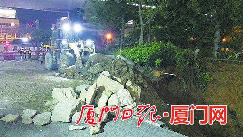 一辆挖机用铲?#26041;?#25955;落在边上的石块往塌陷处推下。