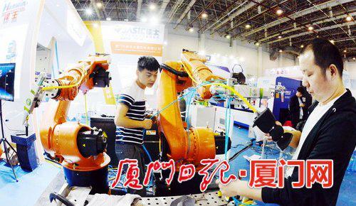 记者探营工博会布展现场,图为工作人员展示焊王工业机器人。