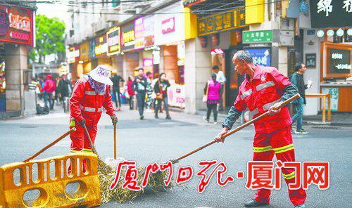 定安路上,环卫工人们来回循环作业,保障路面的持续整洁。