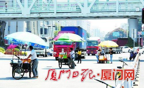 来来往往的大货车车流中,多摊卖盒饭的小贩占道经营。