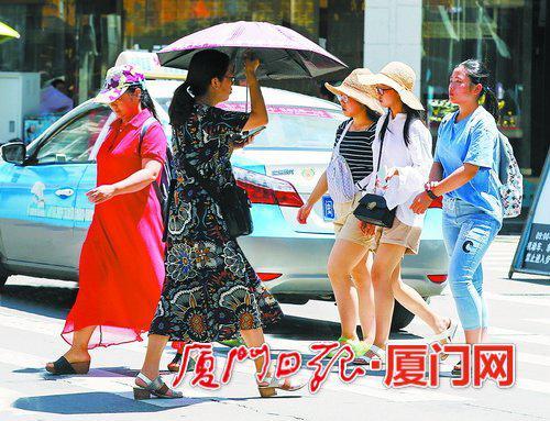 昨日厦门赫赫炎炎,很多行人用帽子和伞遮挡毒辣的阳光。(本报记者吴尔婷摄)