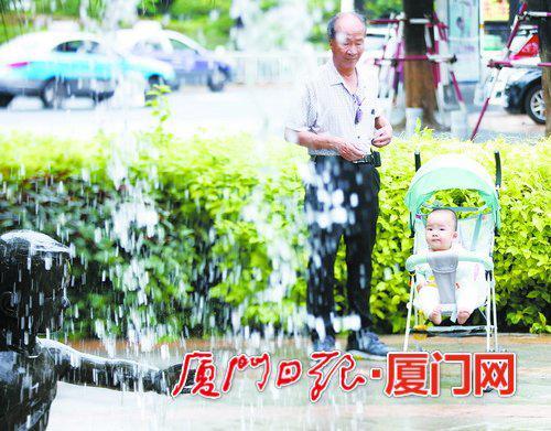 昨日17时许,雨水渐歇,老人带着小孩在筼筜湖畔看喷泉。(本报记者 何炳进 摄)