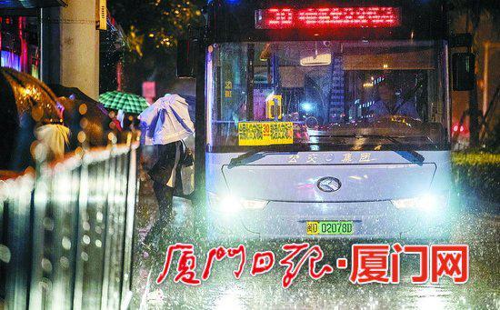 豪雨中,乘客一脚已踏上公交车,仍不愿收伞。(本组图/本报记者 ?#32622;?#40511; 摄)
