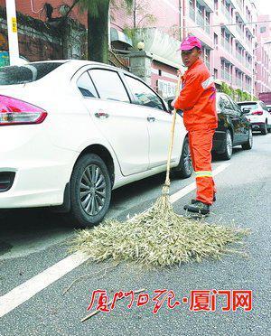 陈绍辉在清扫马路。(本报记者薛尧摄)
