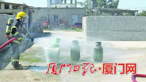 消防官兵对煤气罐进行喷水冷却。