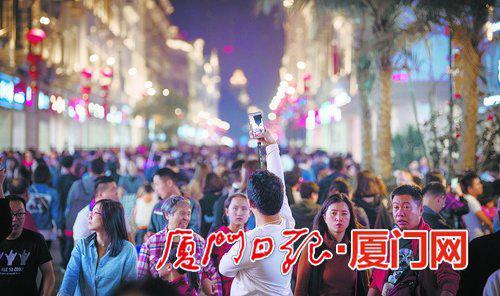 ▲春节假期,中山路游人如织,游客高举手机拍下壮观人流。(本报记者林铭鸿摄)