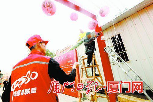 志愿者在现场帮忙布置展台。(本报记者何炳进摄)