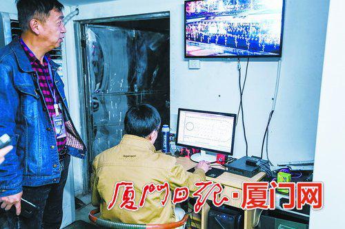 苏炳贤(右)在控制室内操作音乐喷泉播放设备。 (本报记者林铭鸿摄)