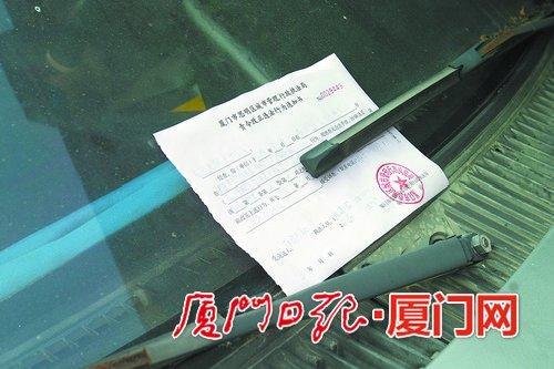 ▲联合整治前,城管执法部门对乱停放的车辆开具责令改正通知书。