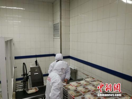 生产车间内工作人员在分拣盒饭。 中新网记者 张尼摄