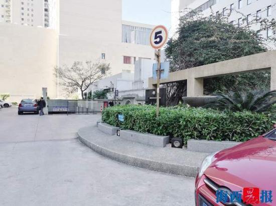 停车收费告示牌面对墙壁,从正常角度看只是一块白色的铁皮。