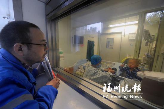 叶鑫鹏爸爸在抽取干细胞前来到移植仓窗口看望儿子。