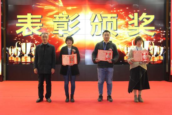 △长富公司副总经理潘永胜(左)给荣获2020年度优秀员工称号的员工颁奖