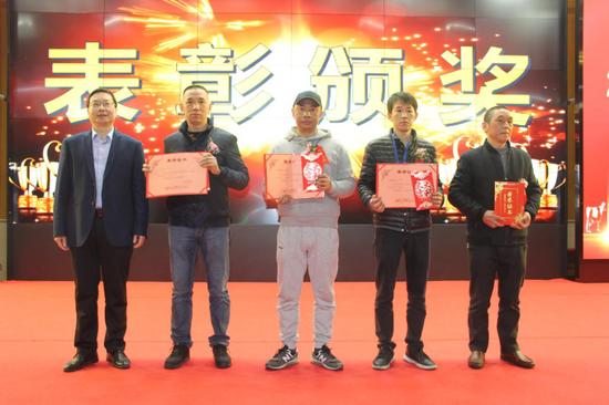 △长富公司总经理助理何水双(左)给荣获2020年度优秀员工称号的员工颁奖