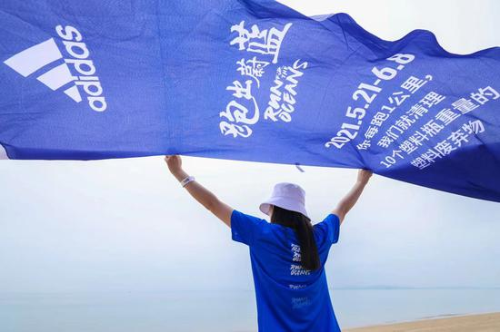 """跑者展开""""跑出蔚蓝""""旗帜,面向大海"""