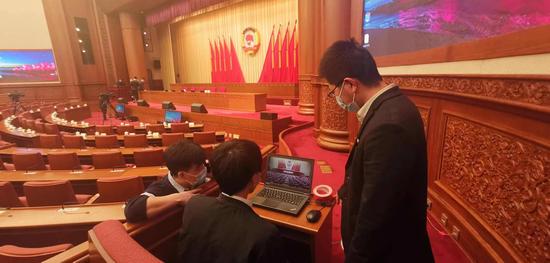 中国联通两会保障人员张杰(图左)、户天硕(图中)、刁志(图右)在全国政协常委会议厅进行大会发言网络直播测试工作。詹益摄