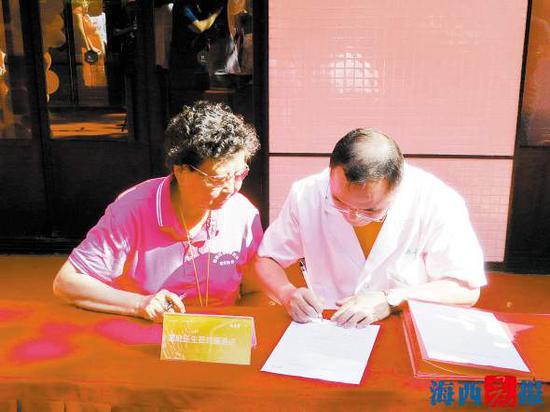 居民代表与德善堂家庭医生代表签署服务协议。记者黄伊娜摄