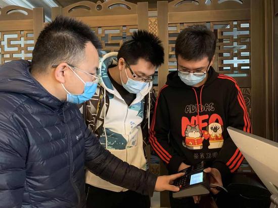 中国联通两会保障人员唐剑波(图左)、朱博(图中)、刘天昊(图右)在代表委员驻地测试大会签到用餐系统。詹益摄