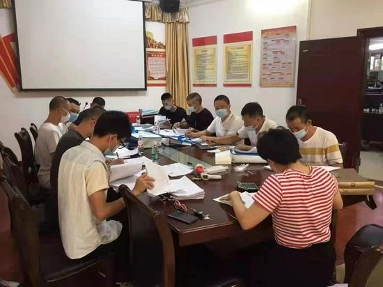 詹来旺(靠门第一个)与同事在一起对材料进行再核对