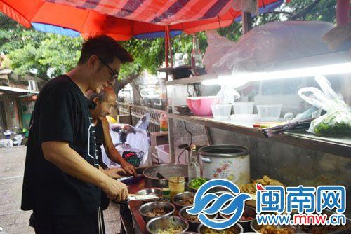 在摊前,陈浩民挑选菜品。