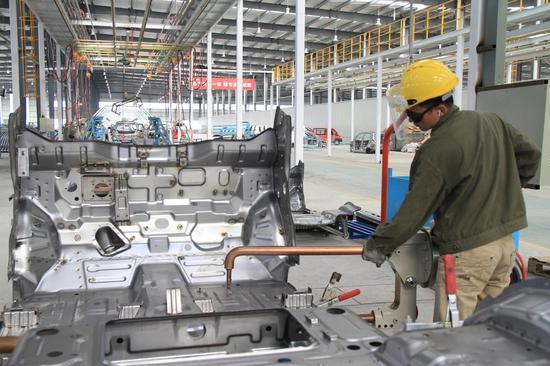 焊装车间里,工人们正在焊接汽车零件。肖和勇 摄