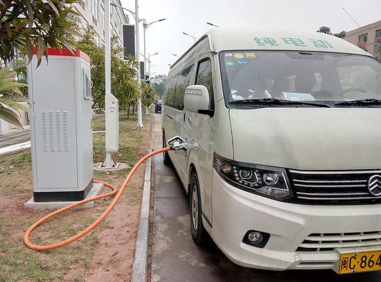 图为一部纯电动中型汽车在使用富顺光电开发的充电桩充电 企业供图