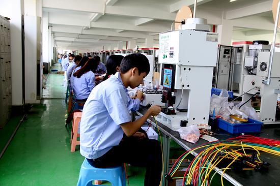 图为富顺光电充电桩生产车间内,工人正在装配产品 企业供图