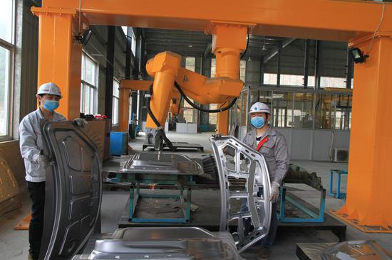 冲压车间里,正在进行激光切割作业,两名工人展示汽车构件切割前后对比。肖和勇 摄