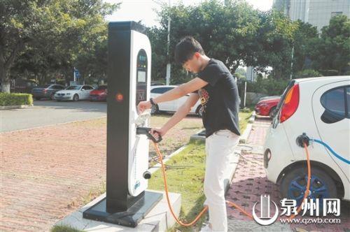 市民使用充电桩为电动汽车充电