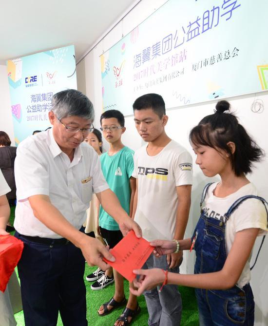 同安区慈善会副会长林少斌与海翼集团品牌和公共事务部总经理潘芳奕为孤困儿童代表颁发助学金