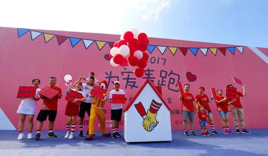 """图为麦当劳福建高级总经理严平(左六)与麦当劳叔叔和爱心家庭代表一起为麦当劳叔叔之家""""添砖加瓦"""""""