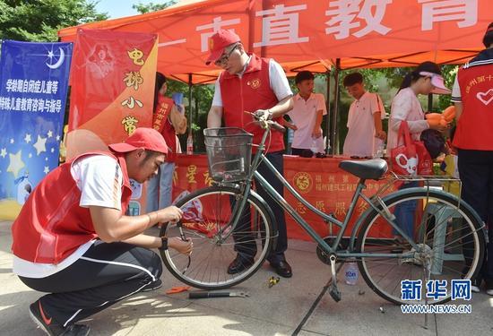 9月24日,福州建筑工程职业中专学校的党团员志愿者在为市民免费修理自行车。