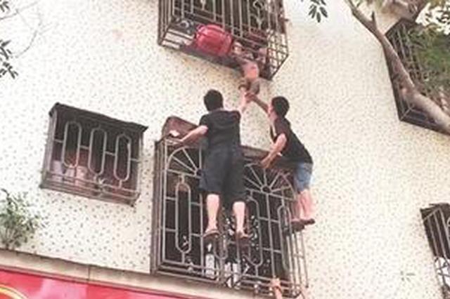 晋江一男童悬空卡在护栏上 两男子登梯托举消防救援