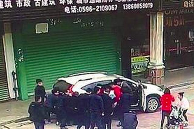 漳州一孩子被压车下动弹不得 众路人抬车救出
