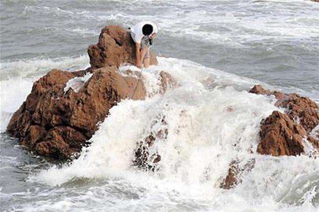 厦门一男子被困礁石 别人着急施?#20154;?#21364;在听音乐玩手机