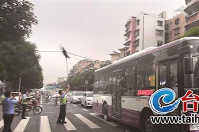 漳州:过街电缆线被车刮落 交警举扫把车流中撑1小时