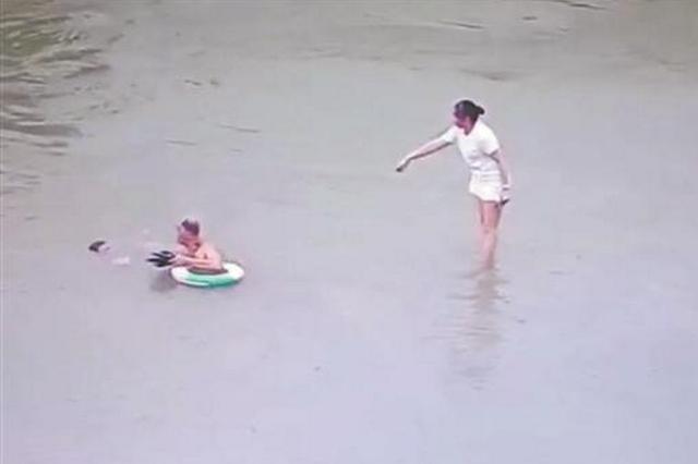 妈妈带孩子江边玩水只顾看手机 孩子落水被冲走